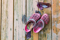 Old garden shoes on wooden deck floor pair of dirty red Royalty Free Stock Images