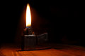 Old gasoline lighter with flame on wooden table against dark background Stock Photography