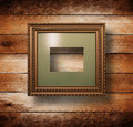 Old gilded wooden frame on grange wall Stock Image