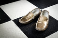 Old golden shoes on black and white floor background Royalty Free Stock Photos