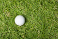 Old golf ball on green grass Royalty Free Stock Photo