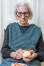 Old grandma slicing and peeling an apple Royalty Free Stock Photo
