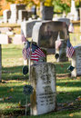 Old gravestones veterans from early wars are still remembered as american flags are placed by them on memorial day Stock Photos