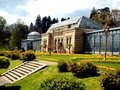 Old green house in beautiful formal garden. in public park with spring flowers in Stuttgart, Germany, Europe Royalty Free Stock Photo