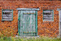 Old green wooden cracked door and windows on a retro red brick wall facade Royalty Free Stock Photo