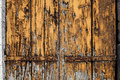 Old grunge worn wooden board with cracked and peeled brown yellow paint.