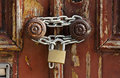 Old grungy wooden door with peeling paint and round door handles chain Stock Photos