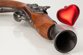 Old gun and red heart on the glass desk Royalty Free Stock Photo