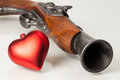 Old gun and red heart on the glass desk Royalty Free Stock Photos