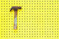 Old hammer hangs on hooks from yellow pegboard Royalty Free Stock Photos
