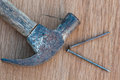 Old hammer with nail on wood background Royalty Free Stock Photography