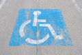 Old handicapped parking sign painted on concrete an and weathered blue Stock Image