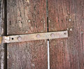 Old hinge a metal on a weathered wooden door Royalty Free Stock Photo