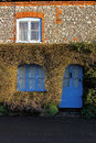 Old house exterior with topiary surround showing blue windows and doors norfolk Stock Photos