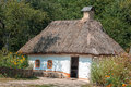 Old house with a thatched roof in the village. Royalty Free Stock Photo