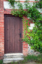 Old house with wooden door and green plants Stock Photos
