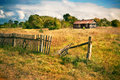 Old house with wooden fence on the empty meadow Royalty Free Stock Photo