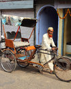 Old indian man rickshaw rolls his bike on street agra india november in agra india nov Royalty Free Stock Photos