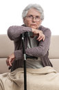 Old injured woman home alone portrait with crutch sitting on couch indoor Royalty Free Stock Photo