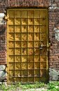 Rusty texture background, old iron door with lattice structure on a red brick wall Royalty Free Stock Photo