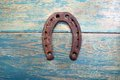 Old iron rusty metal horseshoe on weathered wood Royalty Free Stock Photo