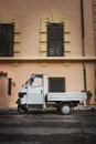 Old italian car parked in a historic building an is the piaggio ape for bee sometimes referred to as ape piaggio apecar Royalty Free Stock Image