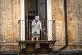 Old italian lady sweeping balcony. Catania, Sicily. Italy Royalty Free Stock Photo