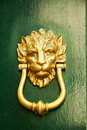 Old Italian lion shape door knocker on green wood Royalty Free Stock Images