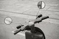 Old italian scooter handlebar with speedometer classical and mirrors sepia toned vintage stylized photo paper texture Stock Photography