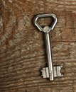 Old key silver on brown wooden background Stock Image