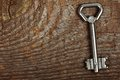 Old key silver on brown wooden background Royalty Free Stock Photo