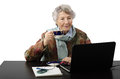 Old lady drinking coffee while reading news on her lepto grey haired smiling woman stares at the laptop screen and Royalty Free Stock Images