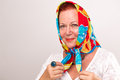 Old lady with her head scarf giving a happy satisfied look in colorful headscarf Stock Image