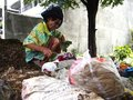An old lady hunts or scavenges for recyclable materials in a pile of trash in an abandoned lot.