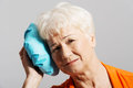 An old lady with ice bag by her head isolated on grey Stock Image