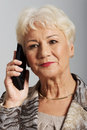 An old lady with mobile phone on grey background Royalty Free Stock Image