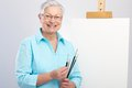 Old lady with paintbrush and canvas happy as hobby painter Stock Photography