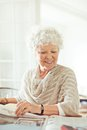 Old lady smiling while reading the news at home Stock Image