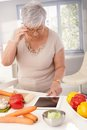 Old lady using tablet in kitchen contemporary to prepare healthy meal Stock Photos