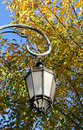 Old lamp against autumn foliage city graceful in park Royalty Free Stock Photo