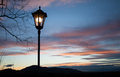 Old lamp post in sunset sky shining Royalty Free Stock Photo