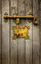 Old latch golden on a wooden door Royalty Free Stock Photography