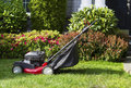 Old lawnmower on front yard ready for work horizontal photo of gas with home in background Stock Photos