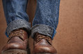 Old leather brown boots and blue jeans Royalty Free Stock Photo