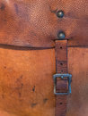 Old leather pouch and worn with belt and buckle used on a vintage motorcycle Stock Photography