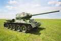 Old legendary tank t at green field sunny summer day Stock Photos