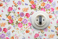 Old light switch on floral wallpaper Royalty Free Stock Photo