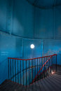Old lighthouse on the inside. Red iron spiral stairs, round window and blue wall. Royalty Free Stock Photo