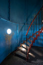 Old lighthouse on the inside. Red iron spiral stairs, round window and blue wall Royalty Free Stock Photo