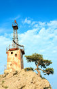 Old lighthouse on rock top on sky background Royalty Free Stock Photography